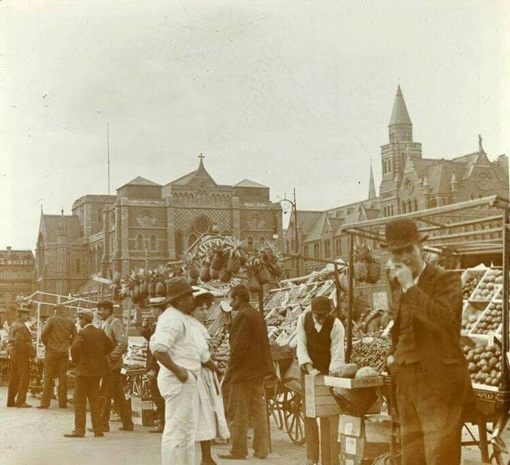 Fruit sellers and hawkers Princes Bridge opposite Flinders St Station 1920's with St Paul's in background.