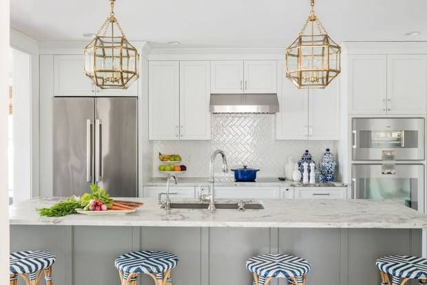 "Holland added large gilded pendants above the island, which provide contrast with the room's stainless steel appliances and hardware. ""Again, don't be afraid if all the finishes don't match,"" she says. ""With all the stainless and chrome in the room, more silver would look flat and not as interesting as the gold."""