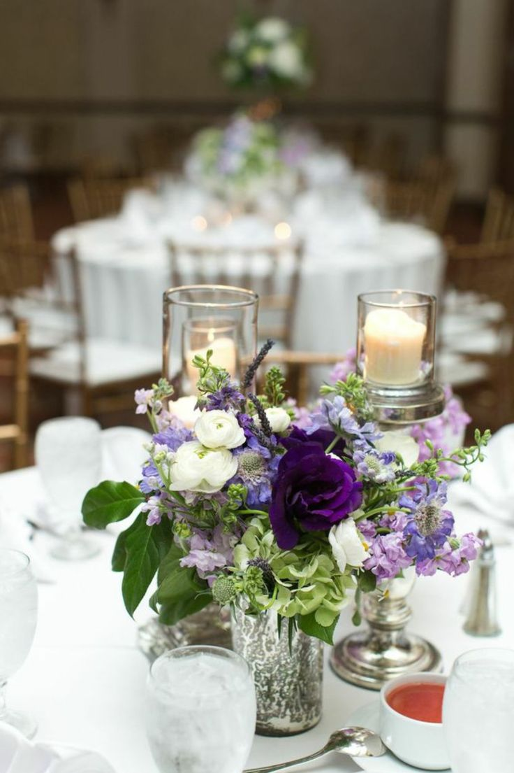 bridesmaids bouquets are repurposed onto centerpieces at the reception. semi structured bridesmaid bouquet of green hydrangea, lavender scabiosa, white ranunculus, lavender stock,  purple lisianthus, lavender, white anemones & lemon leaf wrapped in cream satin ribbon