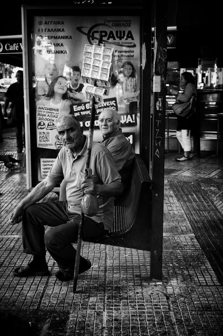 I took this photograph in Pagrati in Athens on Eftichidou avenue. A lottery sales man was taking a rest while sitting on the bench of a bus stop.  I was walking with my best mate. We were laughing about something in a rather loud manner. I saw the lottery sales man look at us disapprovingly, so I snapped a shot in cold blood! Snap!
