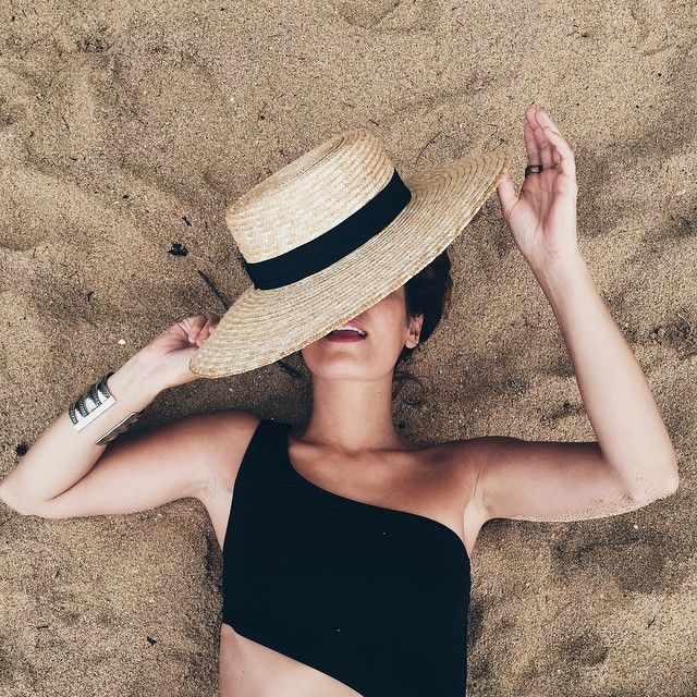 Straw hat with black ribbon and asymmetrical black bathing suit top