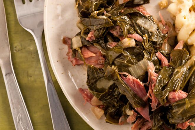 A recipe for collard greens done in the slow cooker and flavored with smoky ham hocks or turkey legs, onions, garlic, chicken broth, and a touch of vinegar.