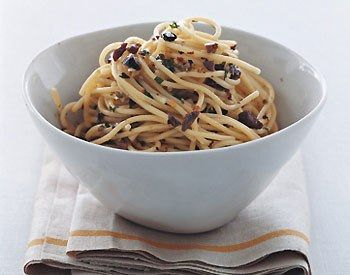 Spaghetti con Salsa di Olive e Pinoli All'arturo                    This pretty, confetti-like dish is sure to become one of your weekday standbys. Not only is it easy to prepare, but you've likely got all the ingredients right there in your fridge. The trick is to hand-chop everything very finely, so that you get just the right amount of fiery crunch in every bite.