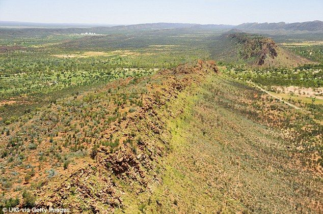 Green pasture after rains in usually arid land with Pine Gap military installation and West MacDonnell National Park beyond
