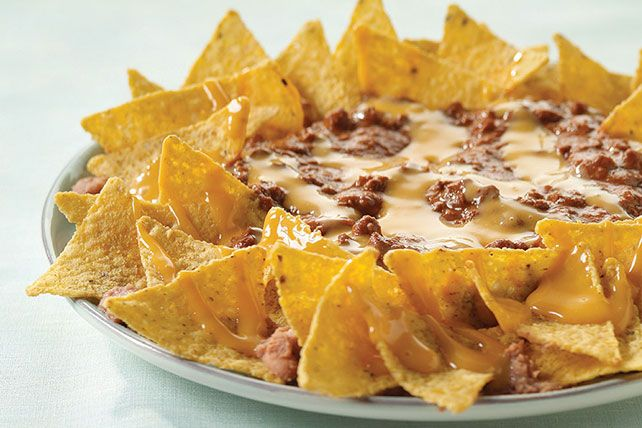 Canned chili and cheese sauce are heated and poured over refried beans and tortilla chips in this hearty snack.