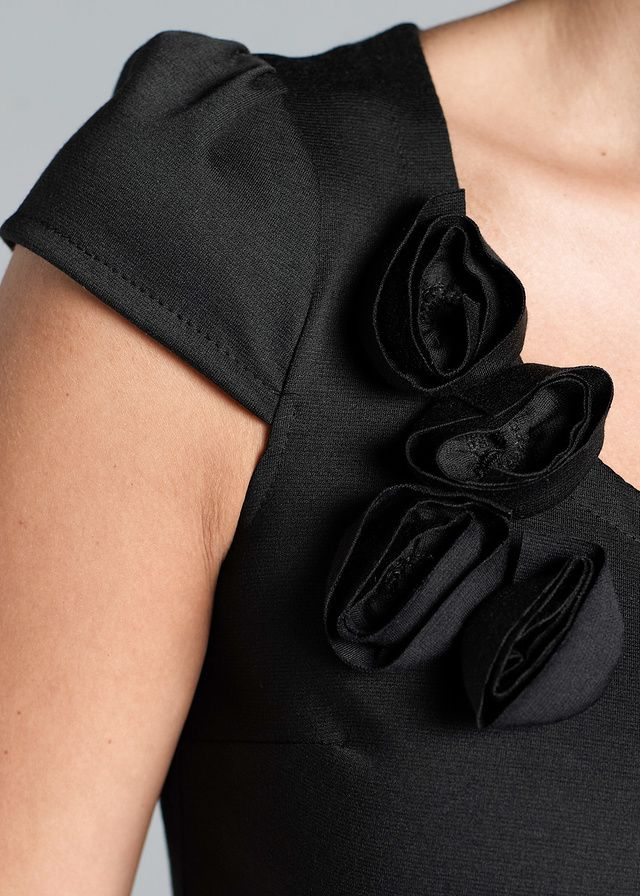 Stílusos ruha kerek nyakkivágással, rövid, puffos ujjakkal és dekoratív, rózsás applikációval a kivágásán. Hossza kb. 88 cm, az alakot kiemelő fazon. Felső anyag: 3% elasztán, 97% poliészter