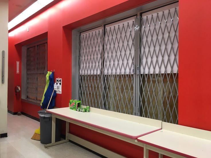 Powder coated gray Xpanda security gates with Slam locks to secure storefront windows.