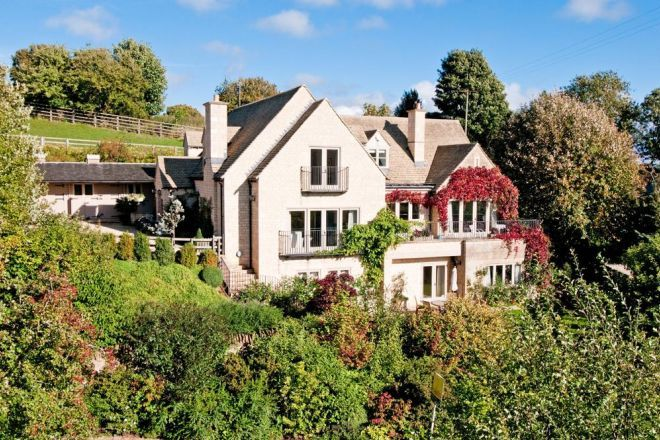 The majestic Glebe House, nestled on the side of a hill in the village of Naunton