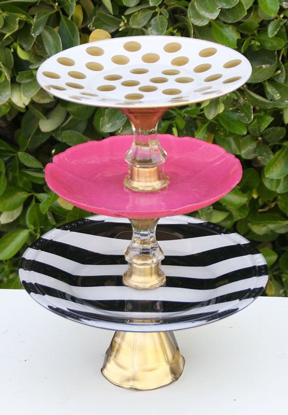 This stand is sold but I can make you a very similar stand.  This cake stand would be the perfect finishing touch for your vintage wedding. This elegant stand is made with one vintage glass patterned plate that are hand painted in Raspberry pink & and two hand painted clear glass plates one painted in black & white strip, the other is painted white with gold polka dots & layered in 3 tiers. The base is a vintage wine glass or goblet.  Plates Measure  10 inches in diameter 7 inches in…