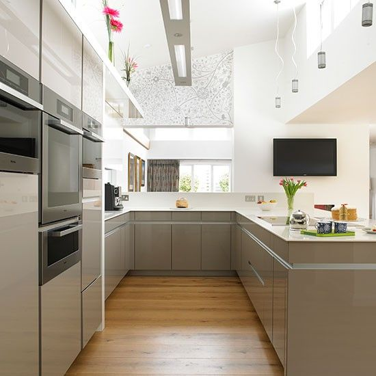 In this contemporary kitchen a wraparound working zone separates this area from the rest of the space without completely closing the cook off.
