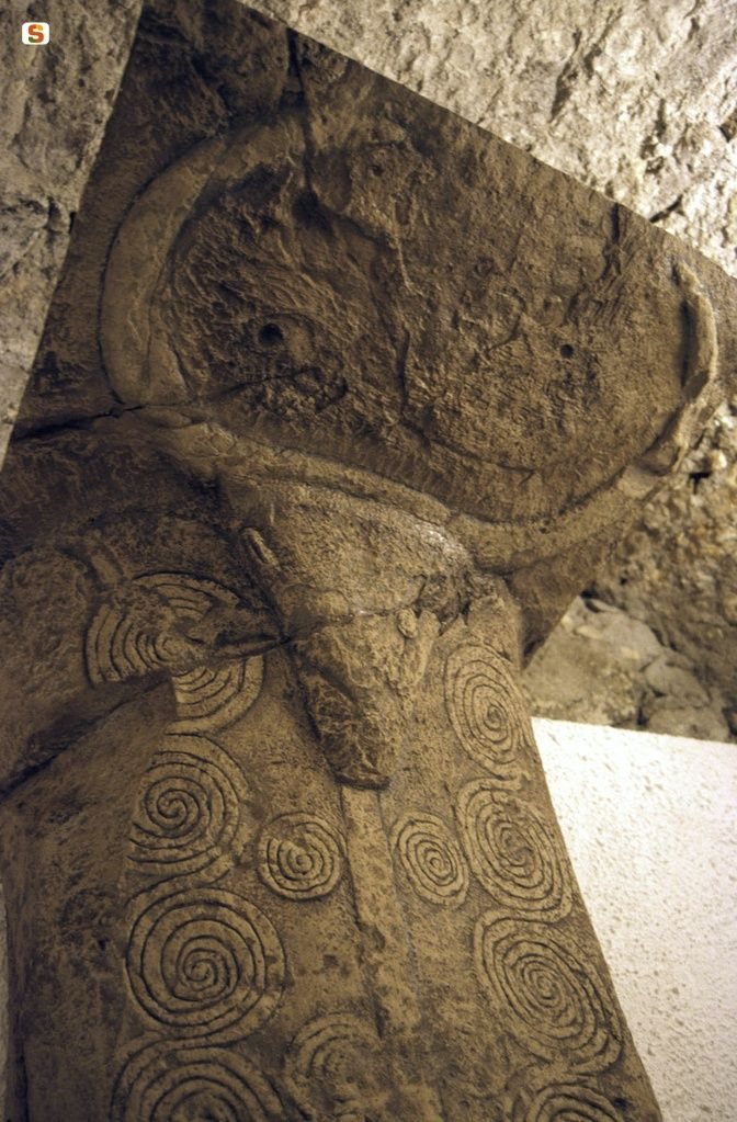 """Sardinia- Bonorva, part of the necropolis """"Domus de janas"""". Tomb 3. Image of a pillar decorated with a bull's head and spirals."""