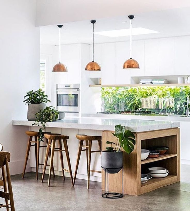 white kitchen, cement floors, copper pendant lighting, white countertops, green plants, wood barstools