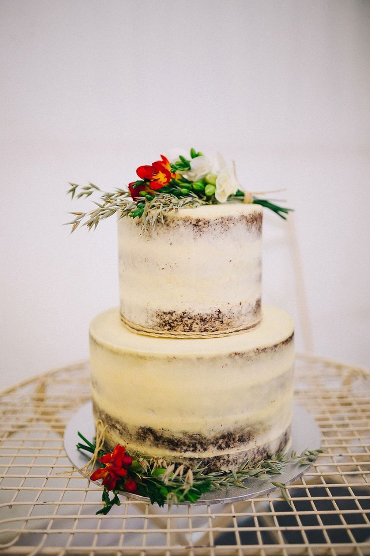 simple lightly iced wedding cake with florals