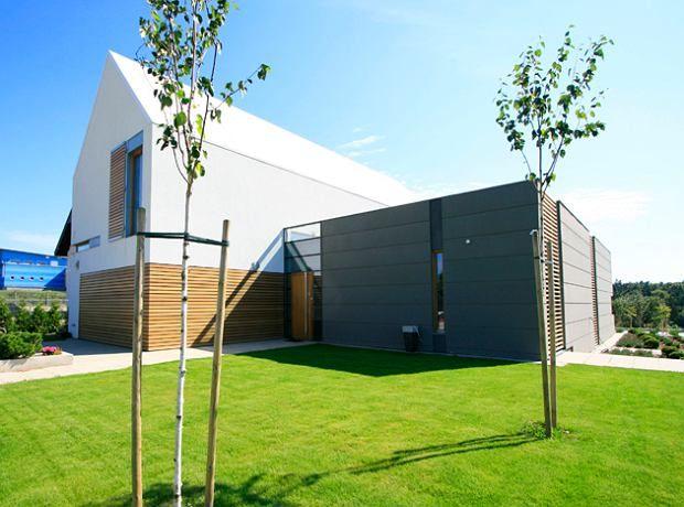 Spadzisty dach ułożony nad jedną z dwóch części bryły domu wykonano w systemie wentylowanej powłoki z płyt włókno-cementowych