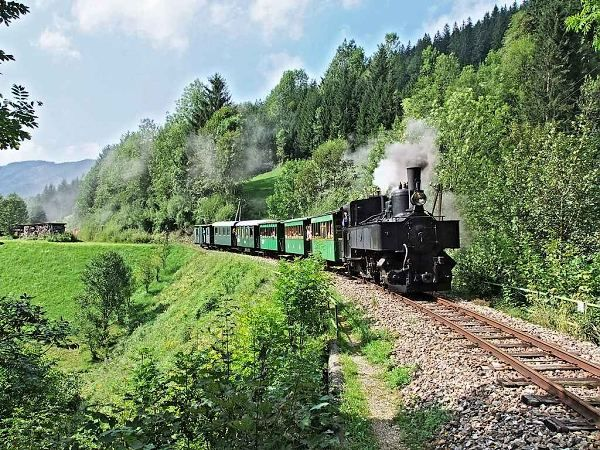 """Ybbstalbahn-Bergstrecke (narrow gauge, 760 mm), Lower-Austria. Picture: The train (with steam engine Uv.1) just left little flag stop """"Holzapfel"""" (background) and is now rolling down to the station Lunz am See"""