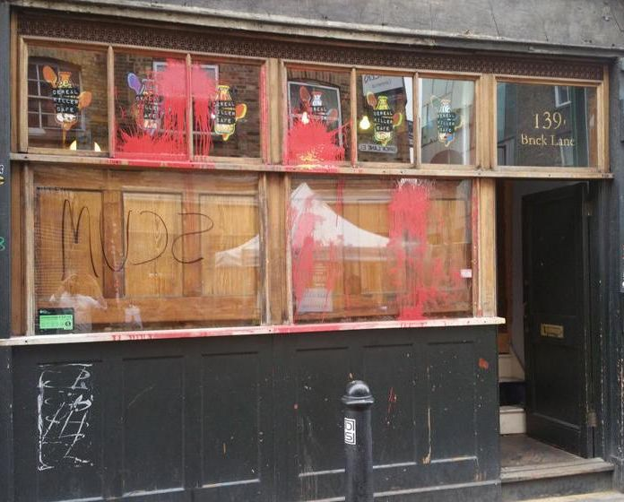 """A mob of masked demonstrators has attacked a """"hipster"""" cereal café in east London, throwing paint at its windowsand daubing """"scum"""" on the walls in an anti-gentrification protest."""
