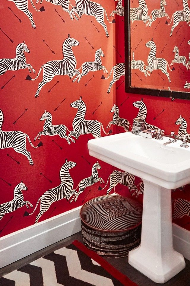 Eclectic bathroom with printed zebra wallpaper and a black mirror