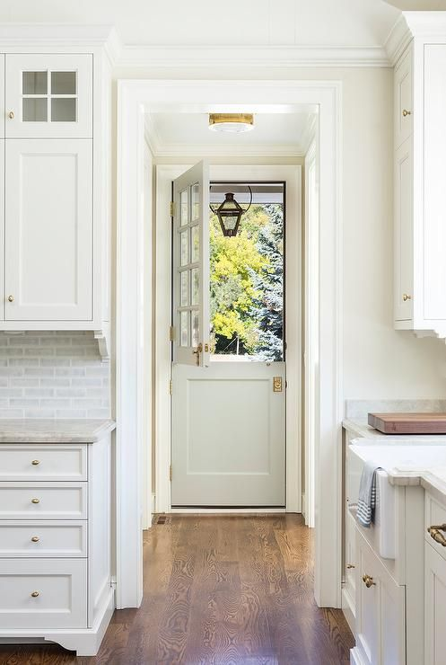 A light gray dutch door is accented with 8 glass panels and antique brass door knobs illuminated by an antique brass flush mount.