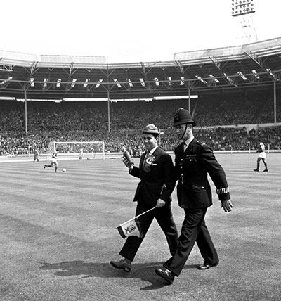 22 May 1963 - Milan v Benfica    A smiling Benfica supporter, carrying a whisky bottle and a flag, is escorted by a policeman from the pitch after running on to greet his team when they took the field
