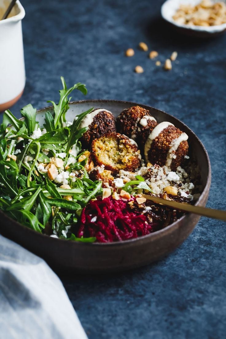 Crispy gluten-free chickpea and butternut squash falafels on a bed of quinoa and arugula with an assortment of flavor-packed salad toppings.