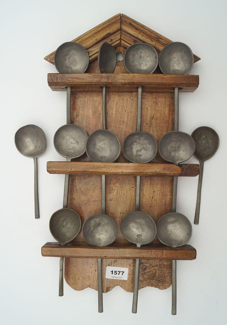 Een lepelrekje met 14 antieke tinnen lepels