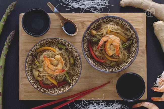 Gli spaghetti di soia con verdure e gamberi sono un piatto orientale: un colorato mix di asparagi, peperoni croccanti e gamberi insaporiti dalla soia