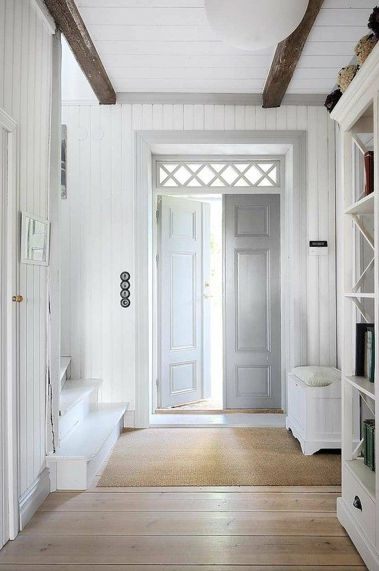 Love:  white entry w/whitewashed doors, natural wood beams, white book shelf, wide-planked pine floors, sisal rug, white painted stairs, transom window above door, beadboard