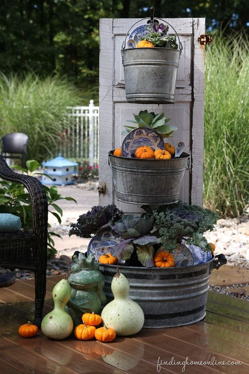 Create a beautiful fall planter from galvanized bins and an old door.