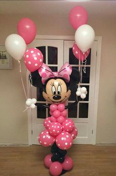 Minnie Mouse balloon sculpture. Love the extra effect that Minnie holds three floating balloons in each hand.