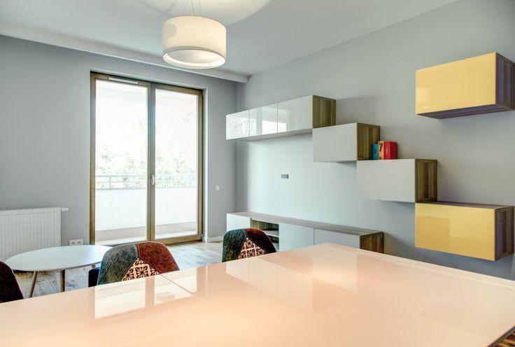 Wnętrze salonu wykończone w nowoczesnym stylu. Wiszące szafki w stylu kubików z kolorowymi frontami zamiast tradycyjnego kompletu mebli. Drewniana podłoga w salonie.