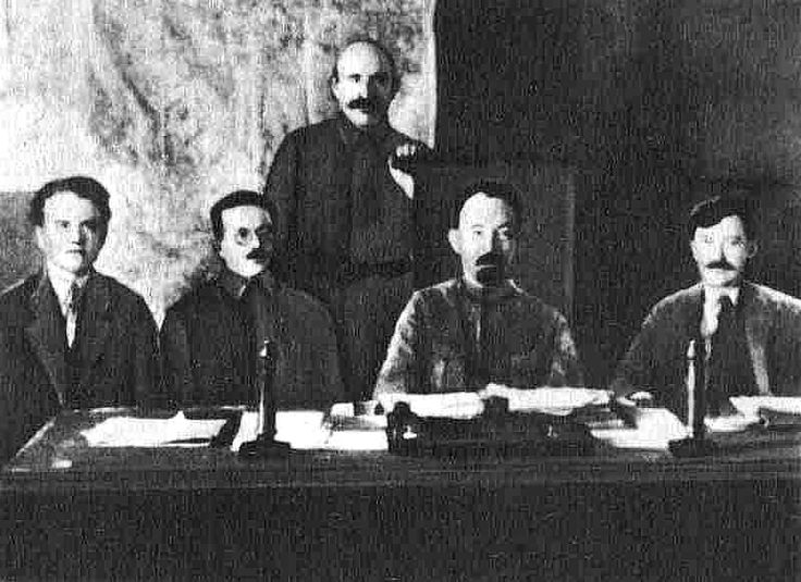 Members of the presidium of VCheKa (left to right) Yakov Peters, Józef Unszlicht, A. Ya. Belenky (standing), Felix Dzerzhinsky, Vyacheslav Menzhinsky, 1921