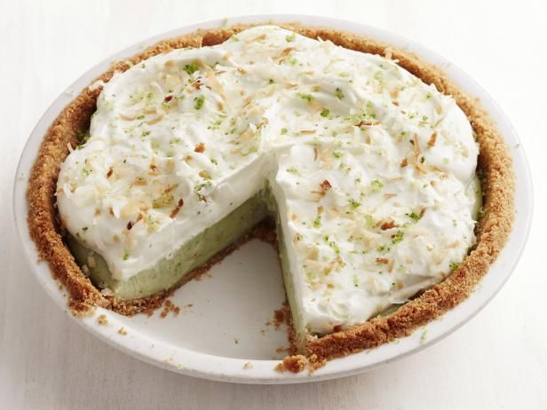 Basil-Mint Coconut Cream Pie Recipe from Food Network | vanilla wafer cookies, sugar, butter, spring, summer, basil, mint, eggs, heavy cream, cornstarch, coconut extract, unsweetened coconut milk, lime zest, shredded coconut
