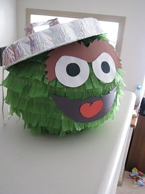 DIY Oscar-the-Grouch pinata ~ make the basic shape, then wrap green crepe paper around and around then fring it to look like fur. The face is just made from construction paper and glued on, and the trash can lid is an inverted tinfoil cake pan with a tinfoil handle that is glued on... so cute!