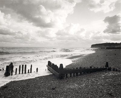 Wooden groynes are shown on a pebble beach in this black and white photograph by fay godwin the location is pett level in east sussex and the photograph