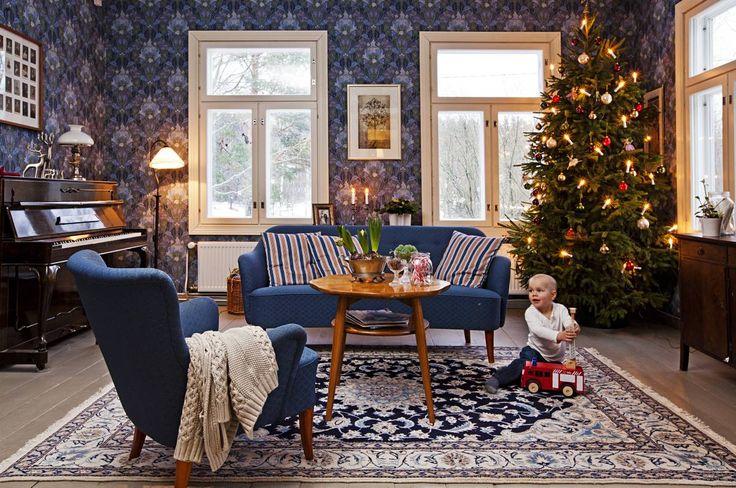 Tummansininen sohvakalusto on 1950-luvulta, ja se on verhoiltu uudelleen noin kymmenen vuotta sitten. Sohvapöytä on Portsan katumarkkinoilta, matto löytyi Ikeasta. Oikealla oleva senkki on peräisin Huuto.netistä. Seinä on tapetoitu Pihlgren & Ritolan William Morris -tapetilla.