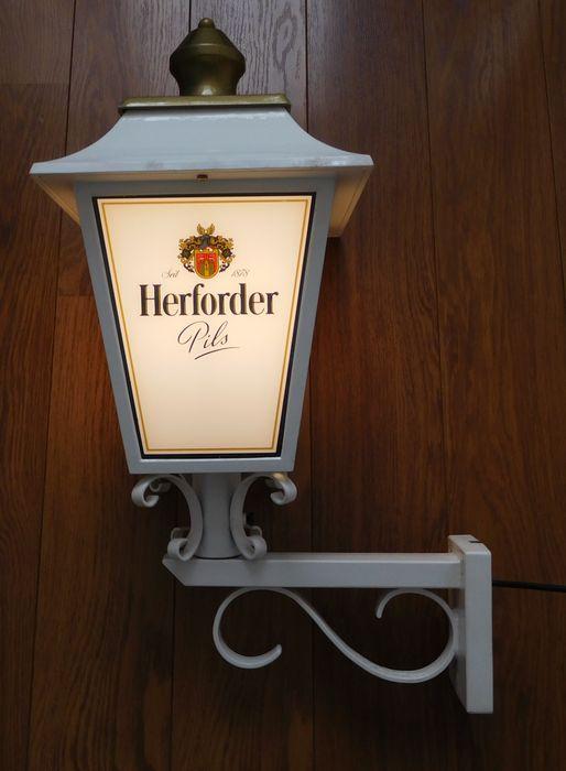 """Metalen """"Herforder Pils"""" Reclame Lantaarn / 2e helft 20e eeuw / Duits  Prachtige Zwaar metalen vierkante """"Herforder Pils"""" Reclame lantaarn (Duitsland) / 2e helft 20e eeuwDeze lantaarn is geheel wit met aan de bovenkant een goudkleurig dakDe lamp heeft aan de 4 zijden kunststof platen met afbeeldingen van """"Herforder Pils""""Verders bestaat de lamp geheel uit metaal en gietijzer en verkeerd in een Heel Goede StaatAfmetingenHoogte - 75 cm.Lantaarndak 30  30 (lengte  breedte)Lantaarndak 50 cm…"""