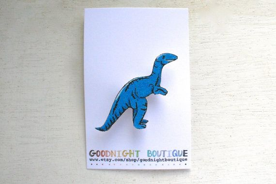This cute brooch is perfect for wearing whilst exploring the jungle, and adds a jurassic touch to any outfit.  This cute brooch is handmade and features my original black ink illustration of a blue Velociraptor on one side and a silver pin, fastened with a blob of glue, on the other. An ideal gift for any fan of dinosaurs, film, and unique quirky jewellery  The dinosaur brooch is made from shrink plastic based upon my own original illustration. Each is individually hand cut, so please note…