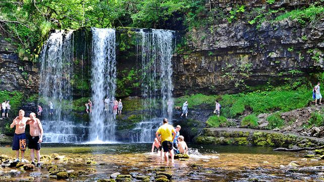 Walkers swimming and walking behind the Sgwd yr Eira waterfall in the Brecon Beacons