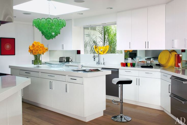 In the Los Angeles home of Elton John and David Furnish, the kitchen's white cabinetry and Corian counters by DuPont are offset by splashes of color from the 1960s Venini light fixture and vases by Lino Tagliapietra, Venini, and Steven Weinberg.