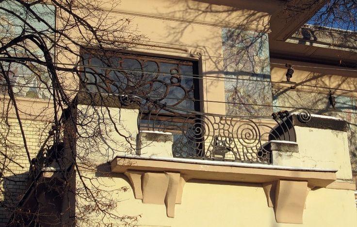 Балкон «Изюминка» дома – решетки на балконах, перекликающиеся с рисунком ограды, древовидные рамы окон и широкая лента мозаичного фриза.