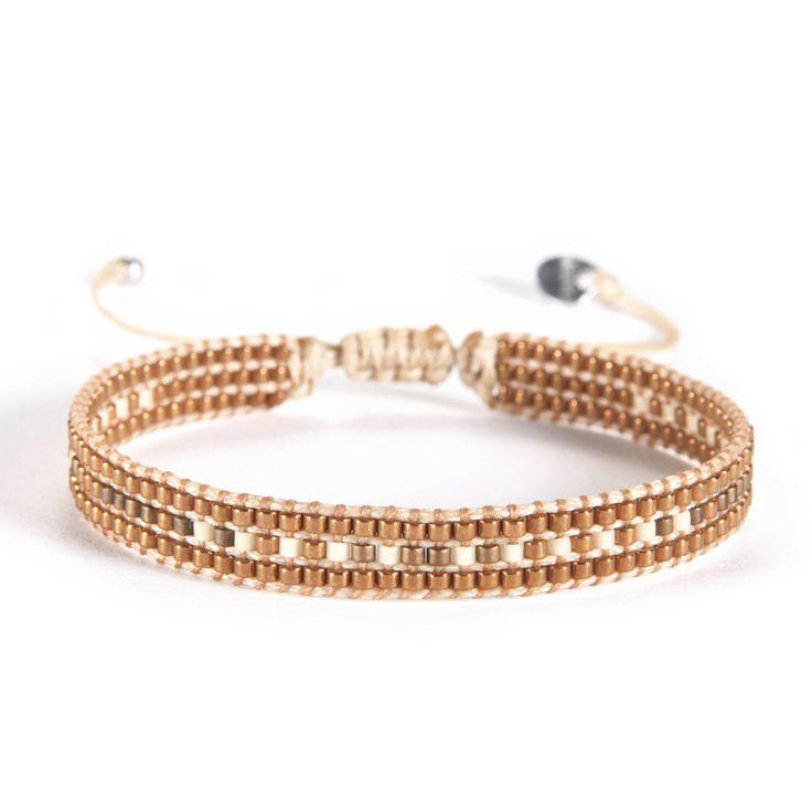 Petit bracelet Mishky fait à la main avec des fils tissés beiges et des perles mordorées. Fermeture par lien de serrage.