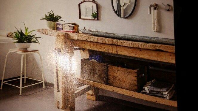 Oude werkbank met trog als wastafel.
