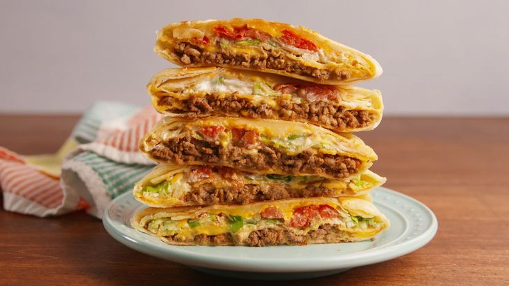 Crunchwrap Supreme    1 lb. ground beef 1 tsp. chili powder 1/2 tsp. ground paprika 1/2 tsp. ground cumin kosher salt Freshly ground black pepper 8 large flour tortillas 1/2 c. Nacho Cheese Sauce 4 tostada shells 1 c. sour cream 2 c. Shredded lettuce 1 c. chopped tomatoes 1 c. shredded Cheddar 1 c. Shredded Monterey Jack vegetable oil Hot sauce, for serving
