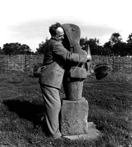 Henry Moore with his sculpture 'Mother and Child' (1953) by Lee Miller. Roland Penrose bought the sculpture in 1937 and positioned it outside his house in Hampstead where its modern form caused a scandal. Here Moore is positioning the sculpture in its new home at Farley Farm.