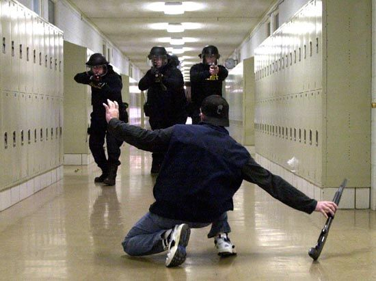 """""""Put it down and get on your knees! Hands on your head!"""" The middle man yelled. """"All right, all right! I'm doing it."""" I slowly lowered myself, setting down the rifle. The damn fools caught the wrong person It wasn't me who started the school shooting. ((I'm the kid, someone be an OC and/or S.W.A.T people. Powers included))"""