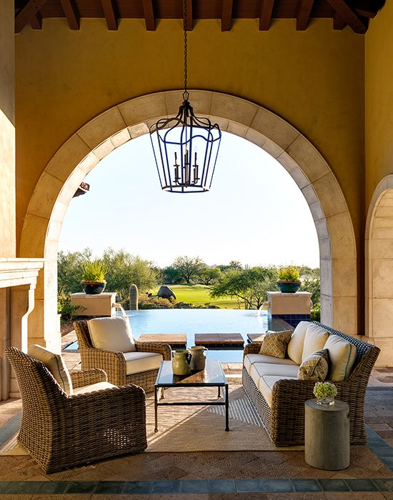 Mediterranean covered patio features a high ceiling accented with an iron lantern over a wicker sofa and a pair of wicker chairs alongside a wrought iron and glass coffee table.