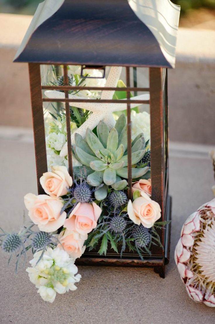 Sukkulenten in einer Laterne kombiniert mit einem Seestern und Blumen