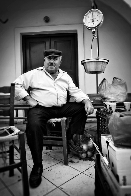 VISIT GREECE| Black and White Portrait in of an older man at a market in Santorini, Cyclades, Greece  © John Bragg Photography