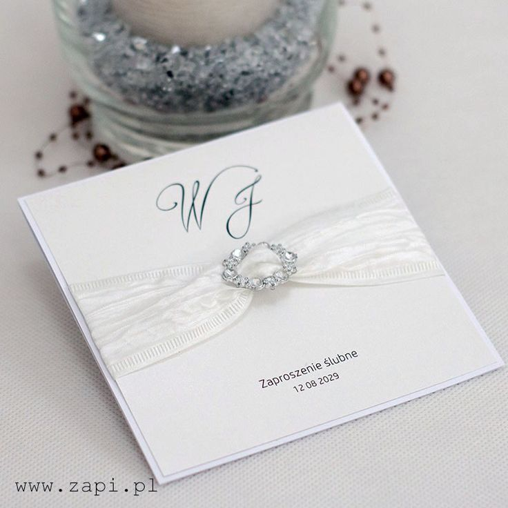 Romantyczne zaproszenie ślubne w kolorze diamentowej bieli. Dekorację stanowi piękna wstążka oraz srebrna klamra.