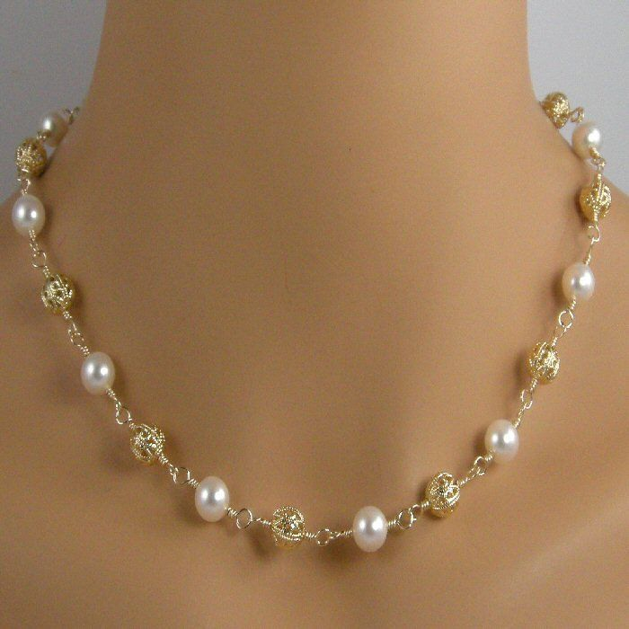 This pretty necklace is made with 8mm 22k gold plate filigree beads and 8mm white freshwaterpearls that are wire wrapped onto 14k gold filled wire. I love t...